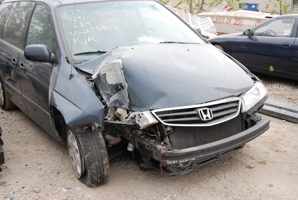 Approach to Honda Odyssey minivan shows frontal collision damage.