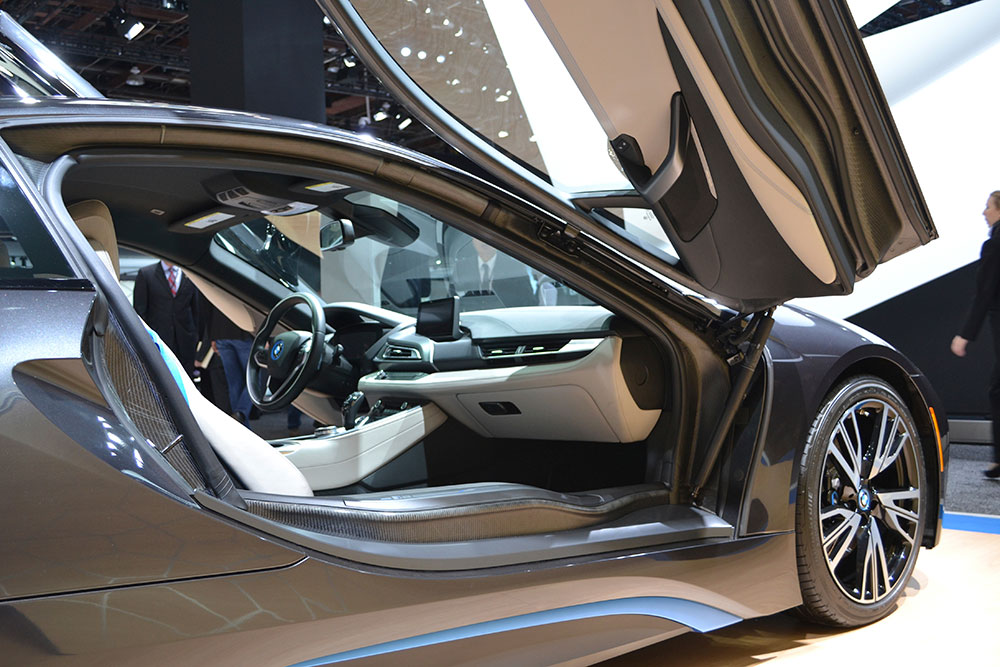 Both doors on the i8 open upward. One part of the door latch is in the normal location along the B-pillar. You can see the loop of the latch in this image on the B-pillar.